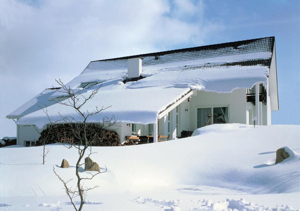Schneemassen bedeuten für das Dach eine zusätzliche Last. Zudem geht eine Gefahr von Dachlawinen aus. Beidem kann man mit der richtigen Ausrüstung vorbeugen. Bild: dach.de