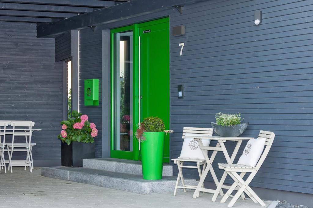 Die grasgrüne Eingangtüre ist ein Blickfang und gelungener Kontrast zur Dunklen Fassade. Bild: Kitzlinger Haus
