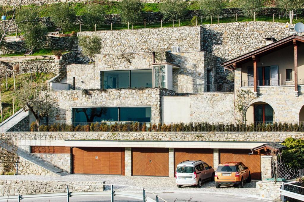 Naturstein aus der Region prägt das terrassiert im Hang liegende private Wohnhaus mit Blick auf das Tal. Bild: Andrea Puliogotto