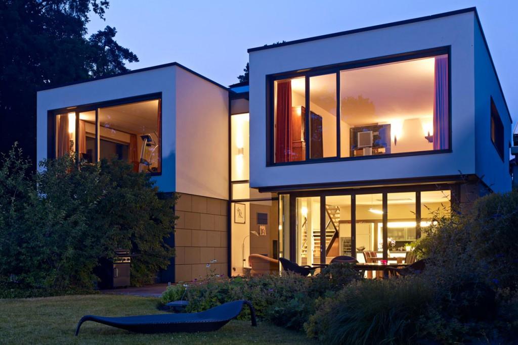 Der Entwurf ist geprägt von dem Bauherrenwunsch, das Gebäude zur Seeseite maximal zu öffnen. In der Abenddämmerung kommen die großen Fensterflächen besonders zur Geltung. Bild: Schüco