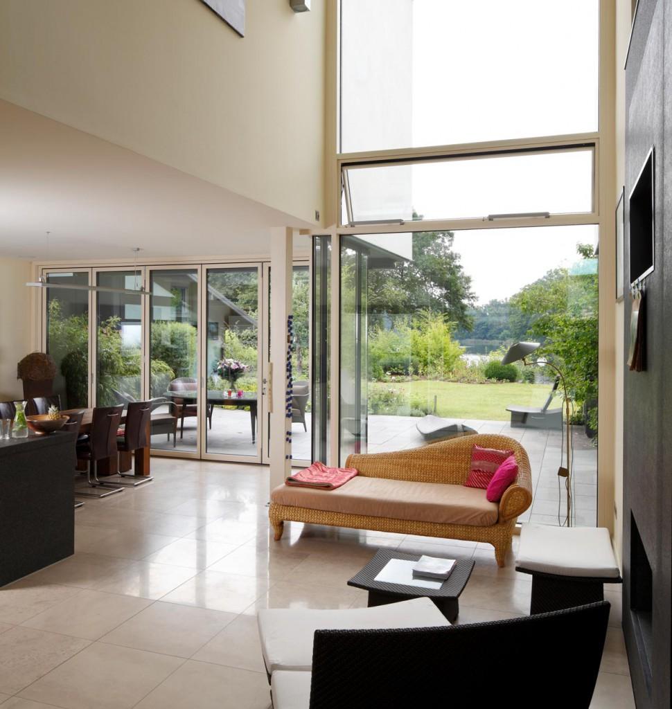 Die Wohnhalle mit Zutritt zur Terrasse und Blick auf den Plauer See: Automatisch gesteuerte Senkklappflügel und Dachluken sorgen für sommerliche Querlüftung. Bild: Schüco