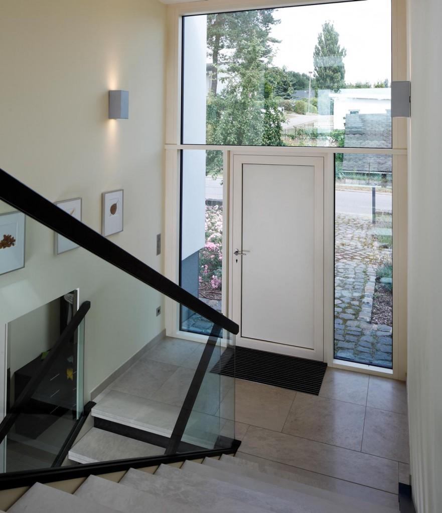 Über den Eingangsbereich werden die beiden obergeschossigen Bauteile und die tiefer gelegene Wohnhalle zentral erschlossen. Die Eingangstür ist mit einem biometrischen Zutrittssystem ausgestattet. Bild: Schüco
