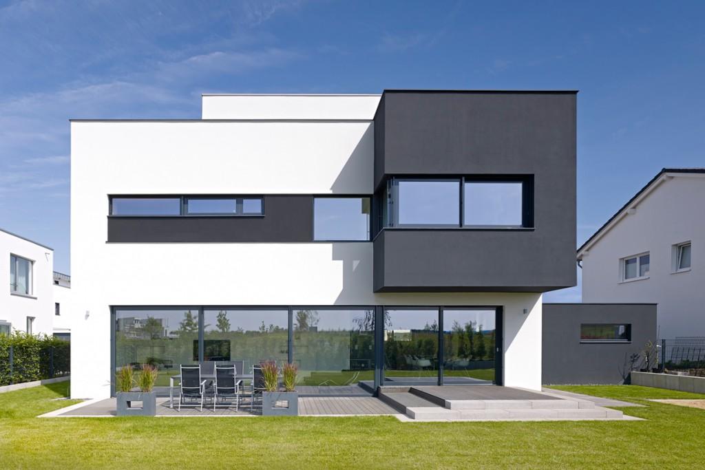 Gartenfassade: Schiebetüren, Festverglasungen und Fensterbänder bilden horizontale Einschnitte in den schwarzen und weißen Raumkörpern. Bild: Schüco