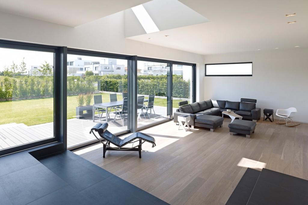 Aus dem Wohnbereich wird über das Schiebetürsystem ein ebenerdiger Zugang zu Terrasse und Garten ermöglicht. Lufträume leiten Tageslicht vom OG ins EG. Bild: Schüco