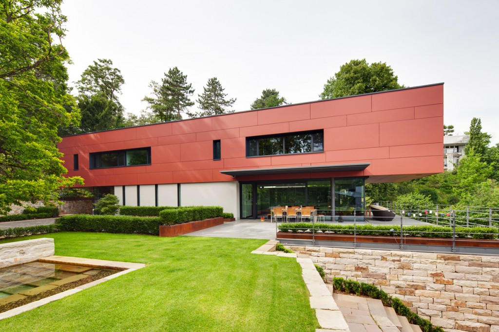 Teil des Entwurfs von Ladleif Architekten, Kassel, ist ein ausgefeiltes Freiraumkonzept mit Sandstein-Trockenmauern und Terrassierungen, das sich organisch dem halbrund ausgebildeten Hanggrundstück anpasst und den Baumbestand integriert. Bild: Schüco