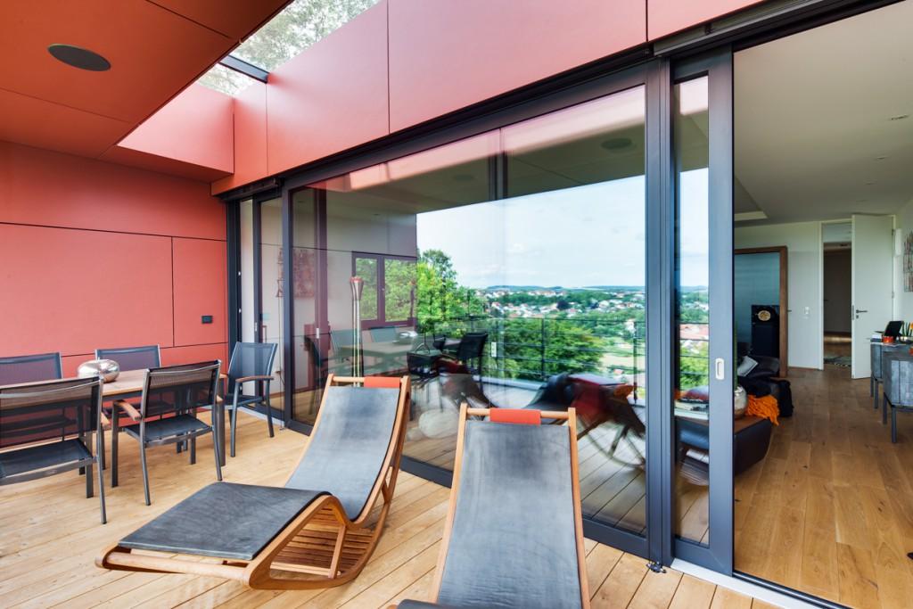 Wohnraum und Terrasse im ersten Obergeschoss: Die großflächige Hebe-Schiebetüranlage ist um Terrassenbreite zurückversetzt, was die sommerliche Erwärmung vermeidet. Zusätzlichen Lichteinfall bietet die Dachverglasung. Bild: Schüco