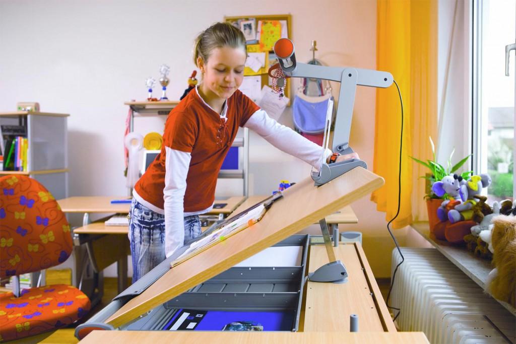 Ein Schreibtisch mit verstellbarer Arbeitsplatte lässt sich hervorragend auf die aktuelle Tätigkeit – etwa Malen, Schreiben oder Lesen – einstellen und beugt dank ergonomischer Vorteile Haltungsschäden vor. Bildquelle: tdx/Moll