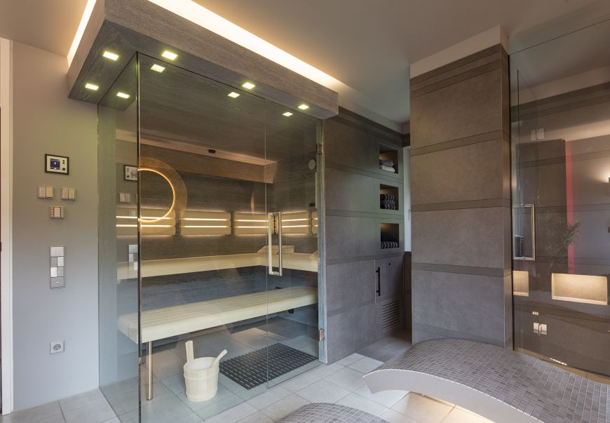 Wellness pur: Die Kabine dieser Design-Sauna ist integriert in ein Privat-Spa mit Rainshower-Dusche und beheizbaren Entspannungsliegen. Die zweiseitige Verglasung bietet Ein- und Ausblicke. (Bild: corso sauna manufaktur)