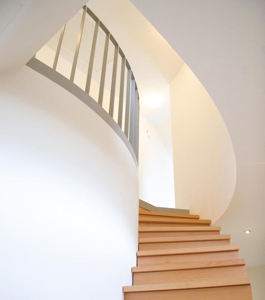 In der geschwungenen Wandscheibe ist ein Einbau eingelassen, der mit einer Schiebetür verschlossen wird. Zwei Kreissegmente als Antritt - in der Materialität des Bodens - bilden die ersten beiden Stufen der Treppe. Bild: Catrin Moritz, Essen