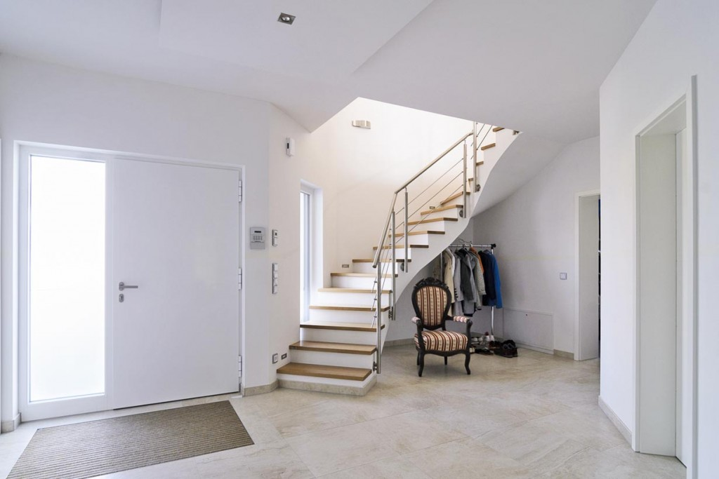 Die geschwungene Treppe passt sich dem ungewöhnlichen Grundriss an. Die bodentiefe Verglasung der Eingangstür akzentuiert außen die Fassade und taucht die Treppe in helles Tageslicht. Bild: Deutsche Poroton, Frank Korte