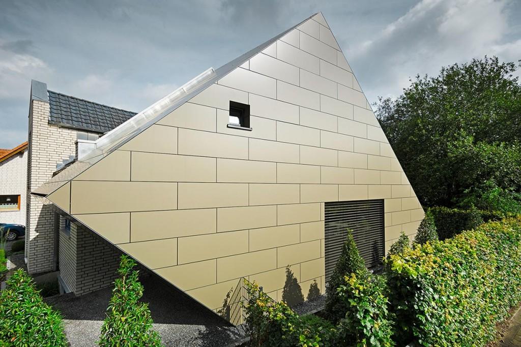 """Der Zubau nimmt die Grundzüge des Altbaus mit Firsthöhe und die Dachneigung des bestehenden Satteldaches auf und sorgt mit einer """"wegkippenden"""" Wand im Erdgeschoss für einen spektakulären Perspektivenwechsel. Architekt Bernd Grüttner entwarf für ihr 15 Jahre altes Wohnhaus einen Anbau, der Wohn- und Schlafraum erweitert und die Optik im wahrsten Sinn des Wortes """"auf den Kopf stellt"""". Bild: Prefa/Croce"""