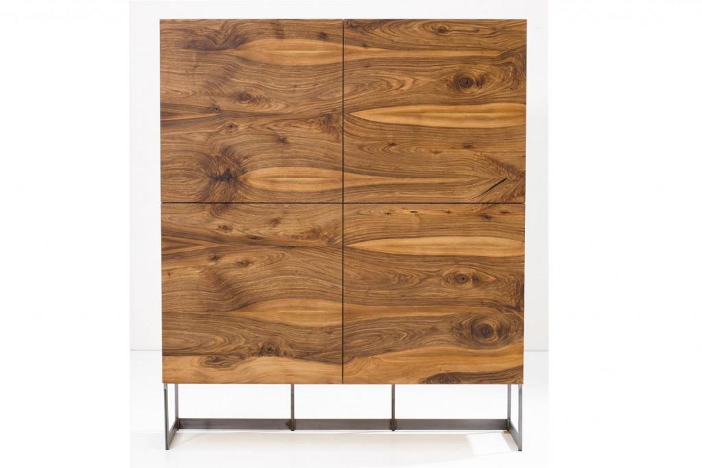 Glatte Fronten, deren Holzmaserung ineinander überläuft, machen den Schrank Divano zu einem Blickfang. Der Effekt wird durch die an den Seiten und oben befindlichen farbigen Gläser verstärkt. Das eiserne Sockelgestell sorgt für einen attraktiven Kontrast. Bild: tdx/Scholtissek