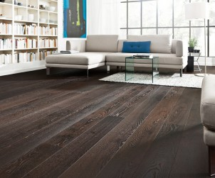 Holz eröffnet viele Gestaltungsmöglichkeiten. Ein dunkler und intensiv gemaserter Holzfußboden setzt einen klaren Kontrast zu den hellen Möbeln und Accessoires im Wohnzimmer. Dadurch entsteht ein sehr edles, repräsentatives Ambiente. Bildquelle: tdx/GD Holz e.V./HARO