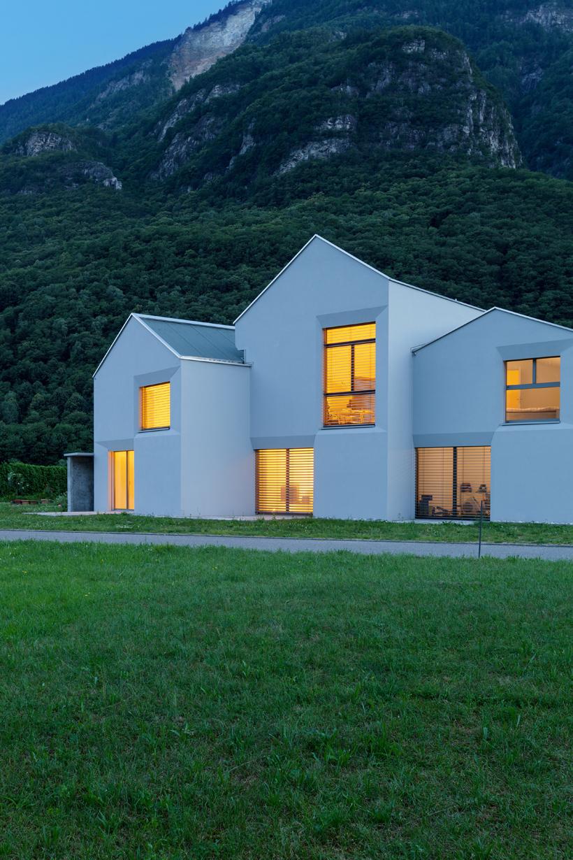 Die Fassade des Einfamilienhauses erinnert auf den ersten Blick an Reihenhäuser. Durch die versetzten Teile passt es sich strukturell an die Berglandschaft im Hintergrund an. Bild: Hausidee.de/Fotolia