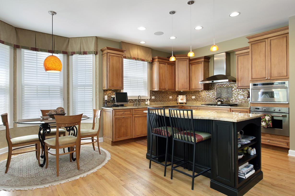 Kochinseln oder Esstheken sind von allen Seiten begehbar und bilden eine formschöne Abgrenzung zwischen Küche und Wohnraum. Beliebtes Material für Küche und Wohnzimmer ist Holz. Wird eine einheitliche Holzart gewählt, entsteht ein rundum stimmiger Eindruck. (Bild: Fotolia)