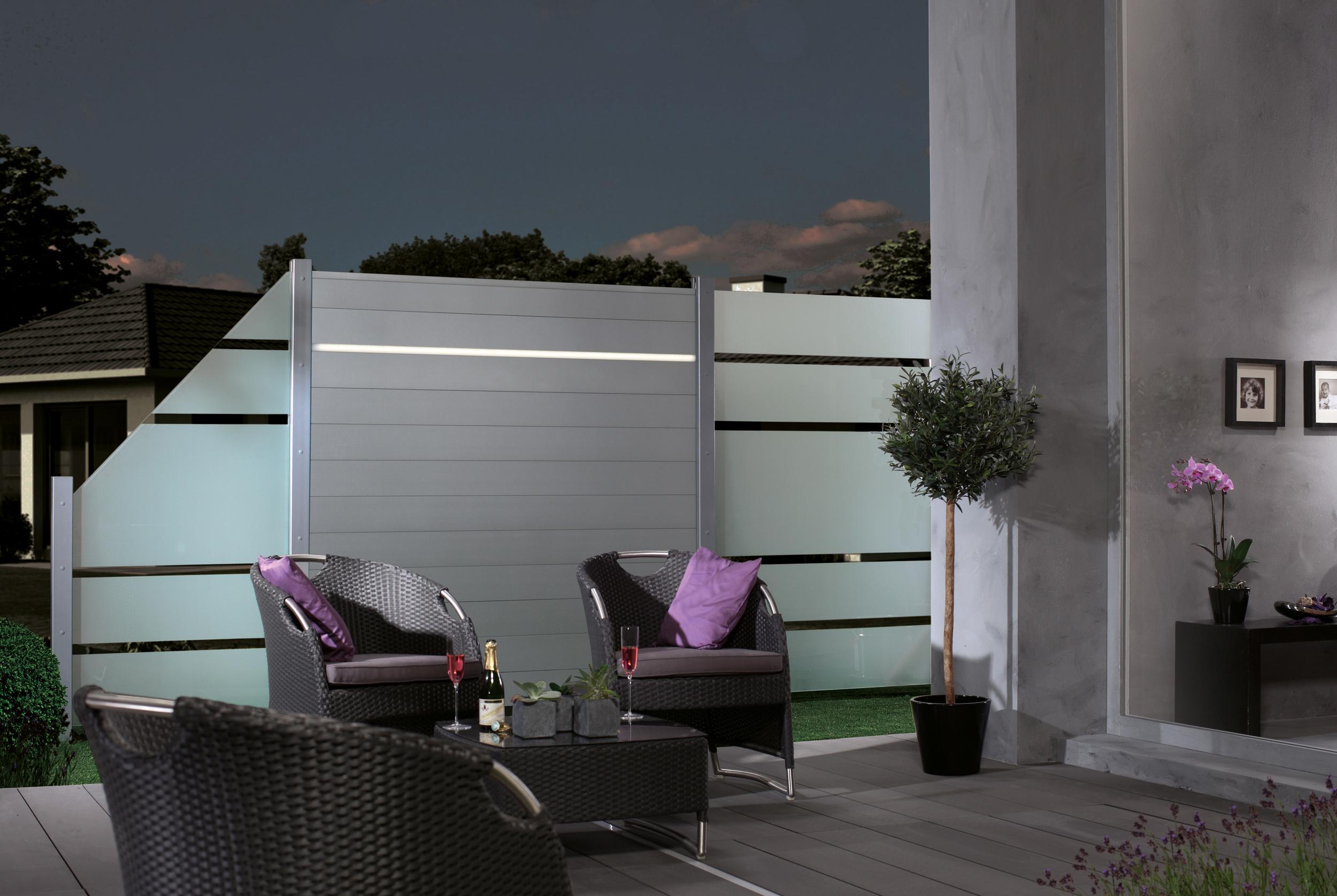 Schutzwände aus Glas sorgen für freie Aussicht und Windschutz zugleich. Kombiniert mit Aluminiumelementen und LED-Streifen wirken sie besonders hochwertig und setzen einen Blickfang im Garten. Bild: Brügmann TraumGarten