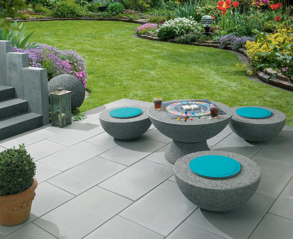 Gartenmöbel aus Stein und Bodenbeläge aus Keramik verleihen Garten und Terrasse eine edle Anmutung. Zudem überzeugen die Materialien durch ihre Widerstandsfähigkeit sowie leichte Handhabe. So wird der Außenbereich zur Komfortzone. (Bild: tdx/Hölzgen)