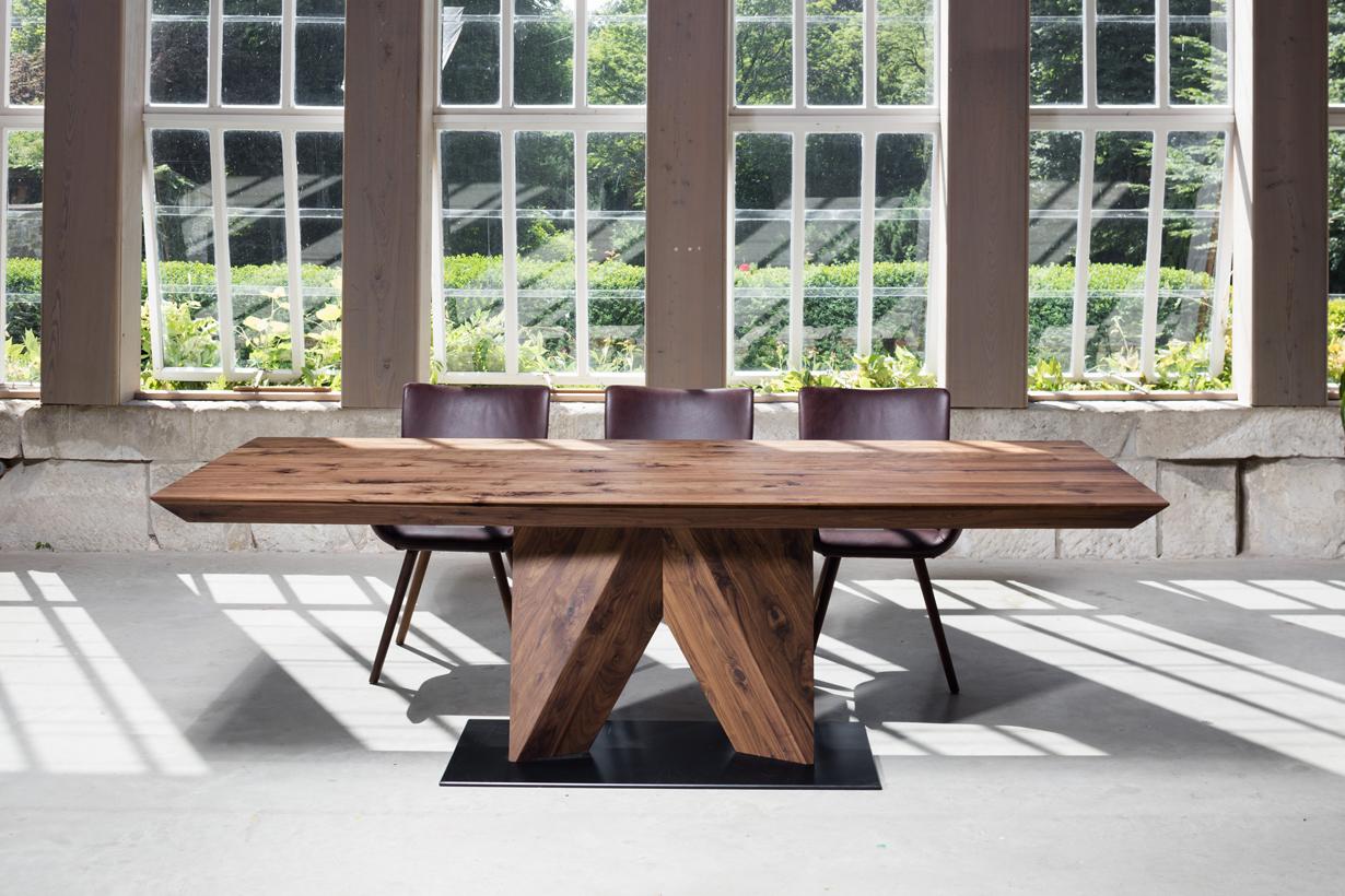 """Der Tisch """"Maurus"""" hat eine betont monolithische Anmutung, um besonders an großen Tafeln mehr Beinfreiheit zu schaffen. Sitzsessel bilden durch ihre gepolsterten Auflagen einen Kontrast zur reinen Naturanmutung der Tische. So wird der Tisch zum Lebensmittelpunkt. Bildquelle: tdx/Scholtissek"""